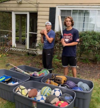 Hendrick Hudson Students Tyler Robinson and Josh Shea with boxes of donated equipment.