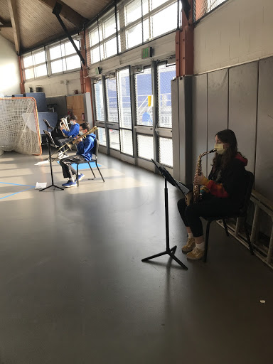 In the dome, trombone, saxophone, and baritone players safely play music together.