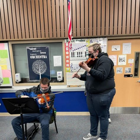 Matthew mentors new musician Damian on how to play the violin.